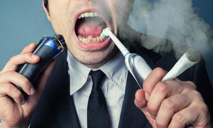Mann im Anzug putzt sich die Zähne, während er einen joint hält