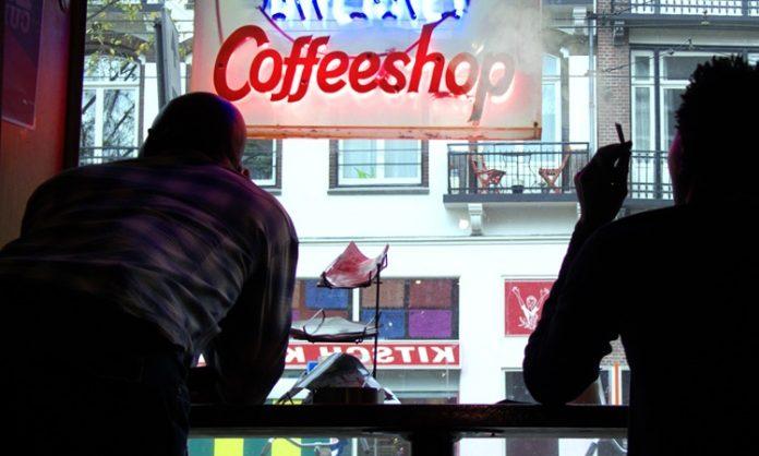 Zwei Gäste blicken aus dem Fenster eines Coffeeshops in Amsterdam