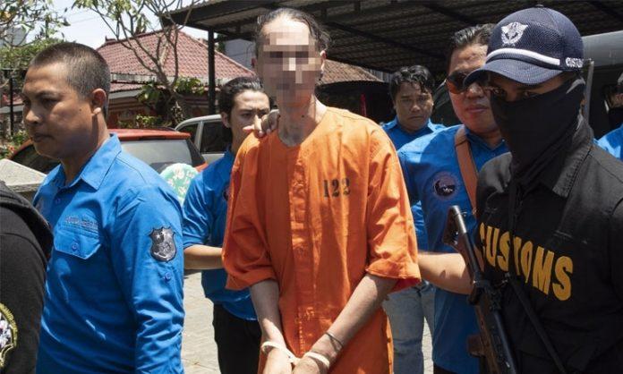 Mann in Häftlingskleidung wird von Polizisten abgeführt