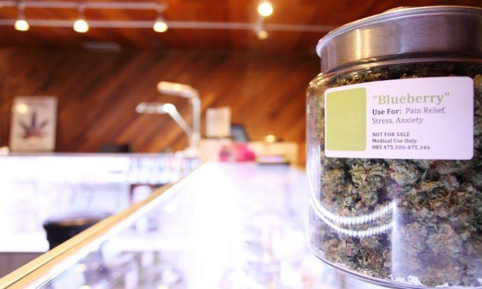 Das Bild zeigt die Theke einer US-Dispensary. Links ein Einmachglas mit Marihuana