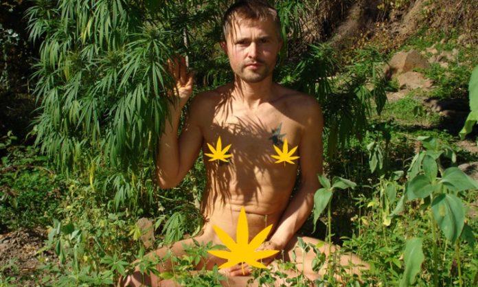 Ein nackter junger Mann raucht Cannabis in der Natur