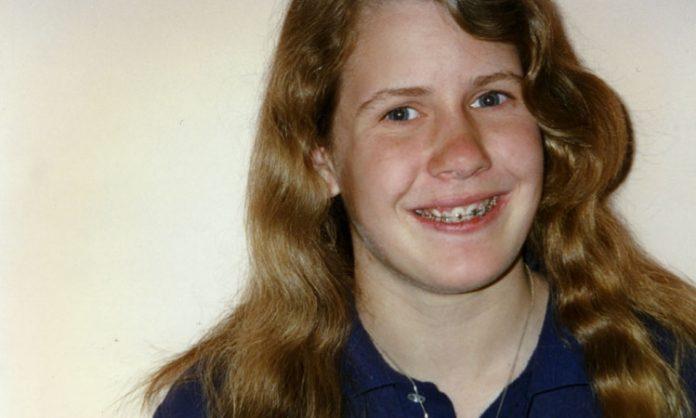 Junger Mensch mit langen Haaren und Zahnspange