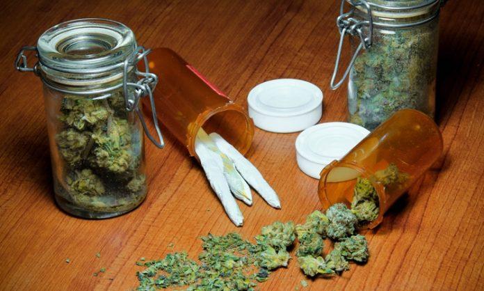 Zwei Einmachgläser mit Marihauna, daneben ein paar Joints und Marihuana-Blüten