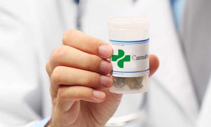 Ein Arzt hält ein Döschen mit medizinischem Marihuana in die Kamera