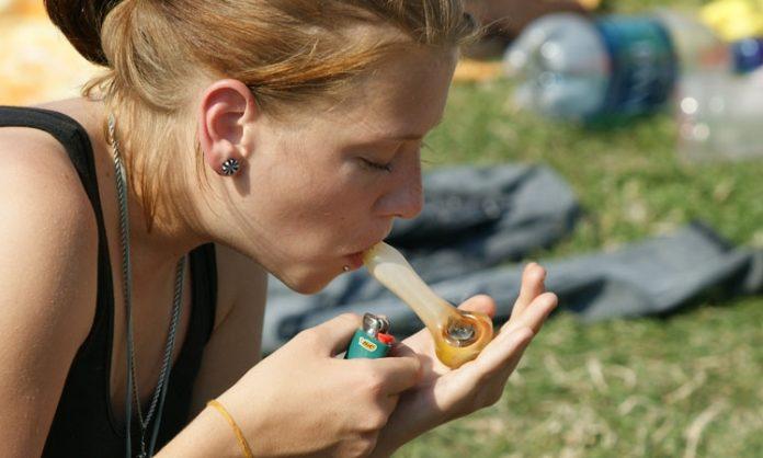 Junge Frau raucht Cannabis in der Pfeife
