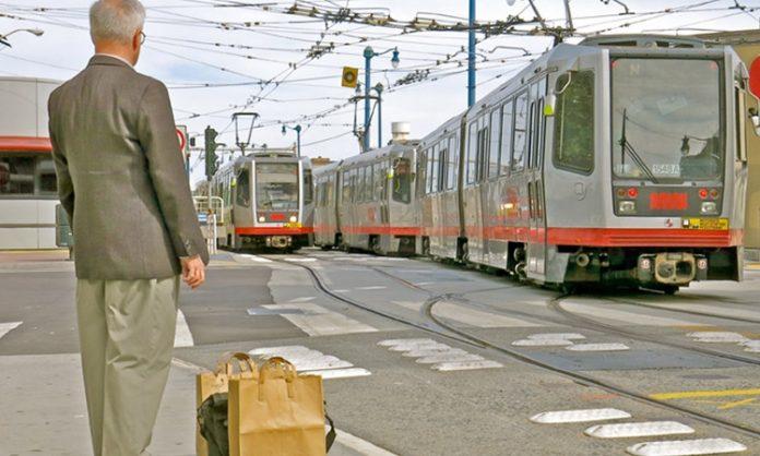Ein Rentner mit Tasche in der Stadt. Im Hintergrund fährt eine Straßenbahn