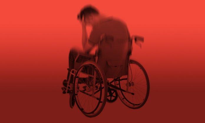 Ein Mann im Rollstuhl vor rotem Hintergrund