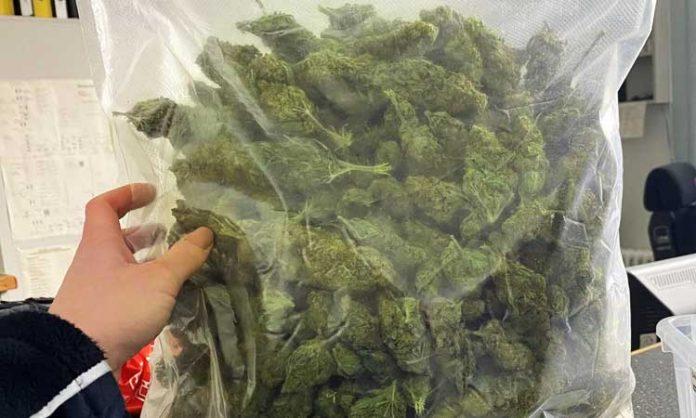 Ein Polizist hält ein Kilogramm Marihuana in die Kamera