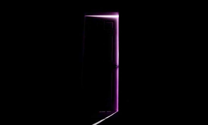 Ein Türspalt, aus dem violettes Licht scheint